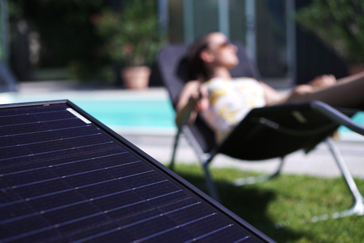Photovoltaikmodul mit Pool im Hintergrund